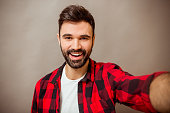 Beautiful young man with a beard in checkered shirt makes self, smiling, on a gray background