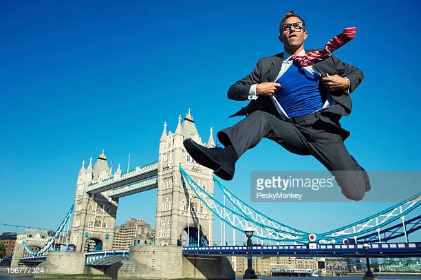 Young Superhero Businessman Jumping Over Tower Bridge London