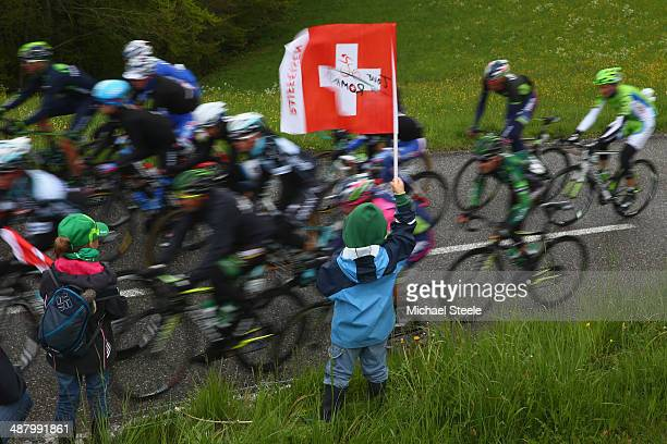 A young supporter flies the Swiss flag as the peloton passes by during stage four of the Tour de Romandie from Fribourg to Fribourg on May 3 2014 in...