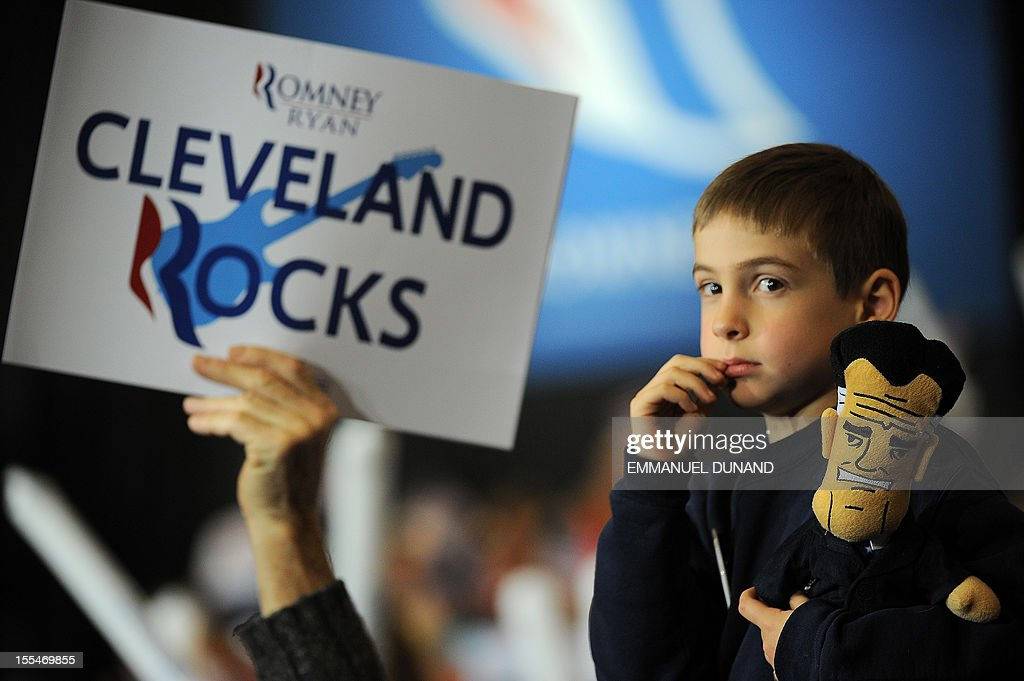 A young supporter holds a puppet of US Republican presidential candidate Mitt Romney during a rally in Cleveland, Ohio, on November 4, 2012. President Barack Obama and challenger Mitt Romney criss-crossed America Sunday, appealing for votes in an agonizing two-day dash for the US presidency that both sides claimed was just within their grasp. AFP PHOTO/Emmanuel DUNAND