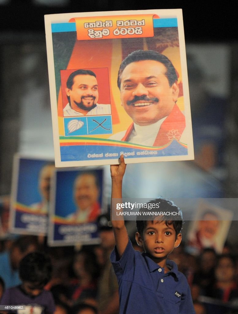 A young supporter holds up a placard with the image of Sri Lankan President <a gi-track='captionPersonalityLinkClicked' href=/galleries/search?phrase=Mahinda+Rajapakse&family=editorial&specificpeople=588377 ng-click='$event.stopPropagation()'>Mahinda Rajapakse</a> during an election rally in the Colombo's suburb of Piliyandala on January 5, 2015. Gunmen shot and wounded three opposition activists who were preparing a stage for President <a gi-track='captionPersonalityLinkClicked' href=/galleries/search?phrase=Mahinda+Rajapakse&family=editorial&specificpeople=588377 ng-click='$event.stopPropagation()'>Mahinda Rajapakse</a>'s chief rival on the final day of campaigning in Sri Lanka's election, police said. The men were hit in a drive-by shooting as they erected a podium for Maithripala Sirisena to address a rally in the southern town of Kahawatte, around 130 kilometres (80 miles) from the capital Colombo.