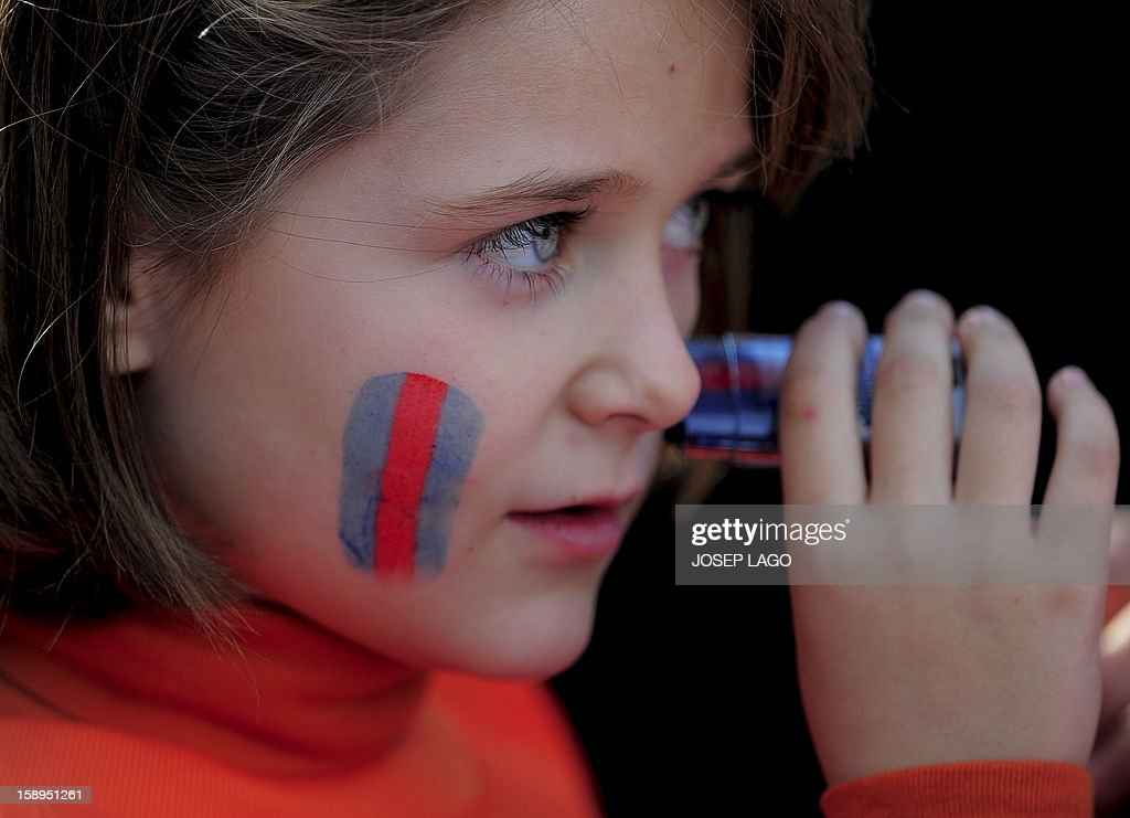 A young supporter of FC Barcelona paints her face with the colours of the club's flag during an open training session at the Mini Stadium in Barcelona on January 4, 2013. AFP PHOTO / JOSEP LAGO