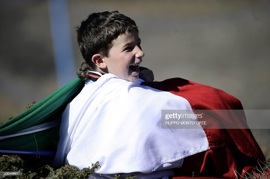 A young supporter of Italy's football team, draped in an Italian flag, watches the team train at a camp in Sestriere on May 24, 2010 ahead of the 2010 FIFA World Cup in South Africa. AFP PHOTO / Filippo MONTEFORTE