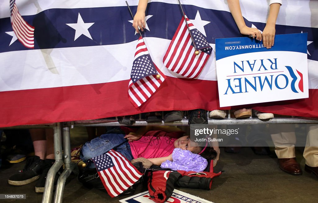 A young supporter of Republican presidential candidate, former Massachusetts Gov. Mitt Romney lays on the ground behind a barricade during a campaign rally on October 27, 2012 in Pensacola, Florida. With less than two weeks before election day, Mitt Romney is campaigning in Florida.