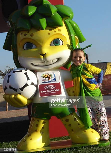 A young supporter of the Brazilian national football team poses with Zakumi the 2010 World Cup 2010 mascot outside Soccer City stadium in Soweto...