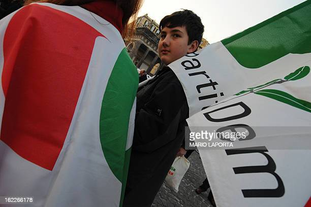 A young supporter of the Italian center left Democratic Party holds a party flag as he and others await the party leader Pier Luigi Bersani during an...