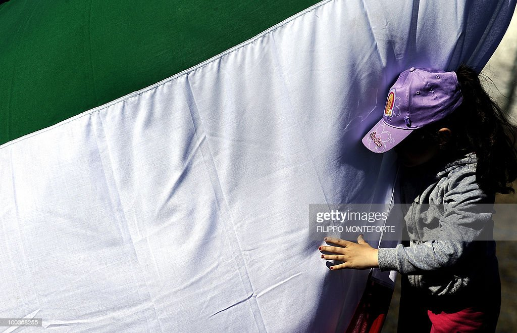 A young supporter of the Italian football team plays with a flag during a training session in Sestriere on May 24, 2010. The italian team are retreating in the mountains of Sestriere before the FIFA World Cup 2010 in South Africa. AFP PHOTO / Filippo MONTEFORTE