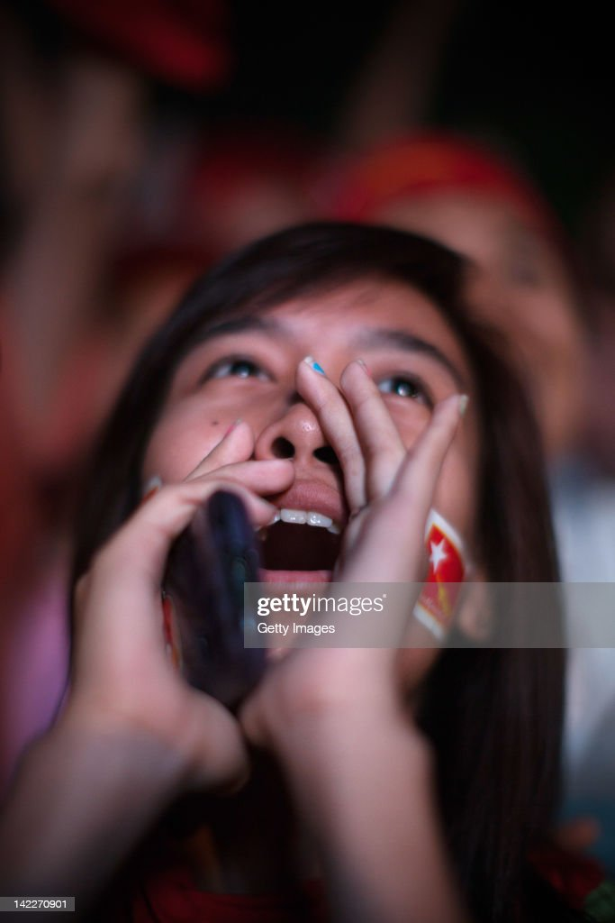 A young supporter of the National League for Democracy wearing party flag stickers her sheeks celebrates preliminary election results coming from the...