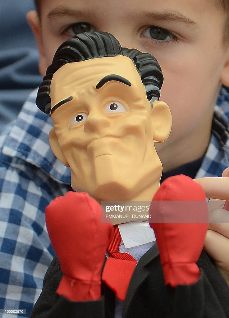 A young supporter of US Republican Presidential candidate Mitt Romney holds a Romney puppet during a rally at Orlando Sanford international airport in Orlando, Florida, November 5, 2012. The marathon for the US presidency is nearing an end as Romney and US President Barack Obama mount last ditch efforts to hold key battleground states, one day before the US presidential elections. AFP PHOTO/Emmanuel DUNAND