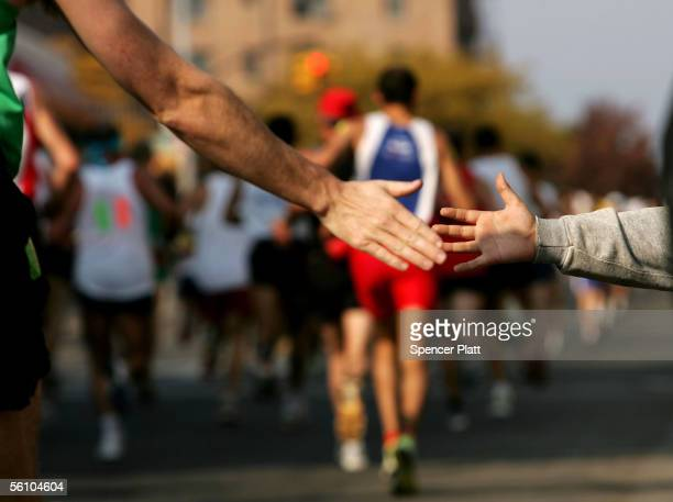 A young supporter reaches out to a runner during the New York City Marathon November 6 2005 in New York City In a final sprint to win the men's title...