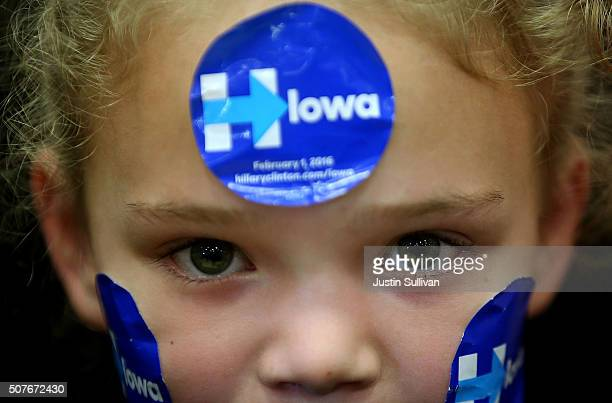 A young supporter wears campaign stickers on her face as democratic presidential candidate former Secretary of State Hillary Clinton speaks during a...