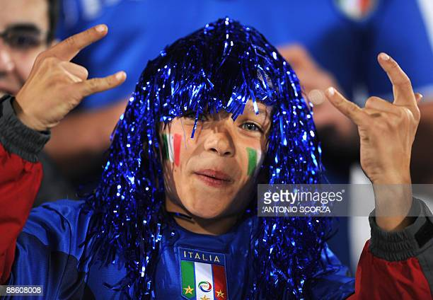 A young supporter with the Italian colours painted on his cheeks gestures in the stands before the Fifa Confederations Cup football match Italy vs...