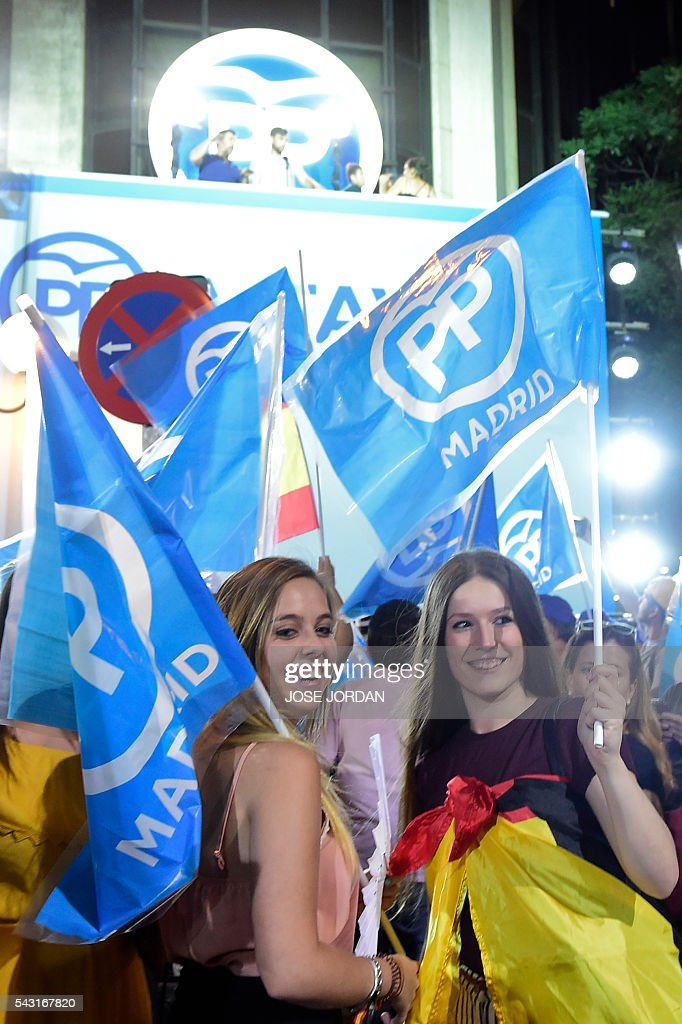 Young supporters of the Popular Party (PP) hold flags as they wait outside the PP headquarters during Spain's general election in Madrid on June 26, 2016. Spain's second elections in six months was due to conclude on June 26 in much the same way as they did in December, with the incumbent conservatives winning tailed by the Socialist party, partial results showed. / AFP / JOSE