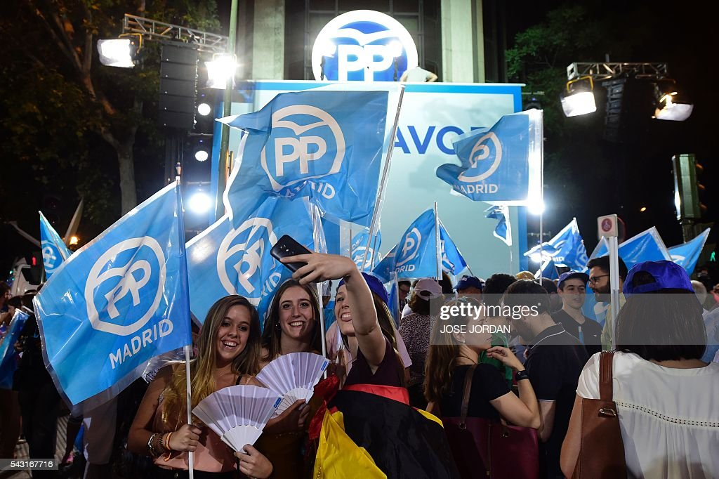 Young supporters of the Popular Party (PP) pose for a selfie as they wait outside the PP headquarters during Spain's general election in Madrid on June 26, 2016. Spain's second elections in six months was due to conclude on June 26 in much the same way as they did in December, with the incumbent conservatives winning tailed by the Socialist party, partial results showed. / AFP / JOSE