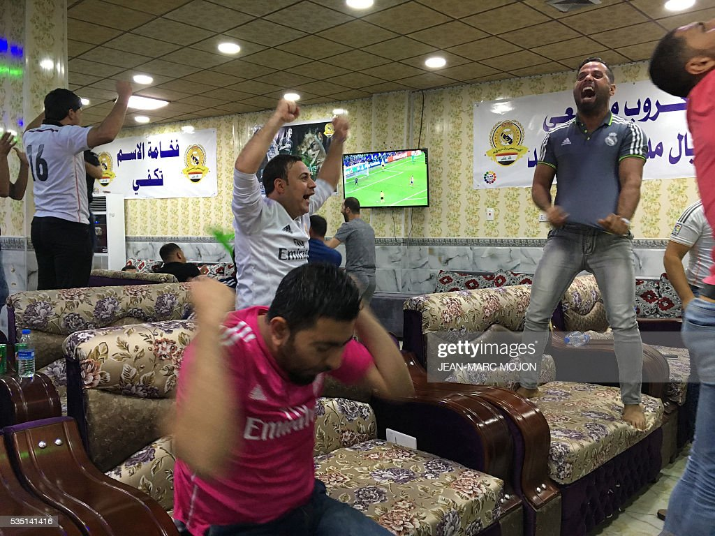 Young supporters of the Real Madrid football club celebrate their team's victory in the Champions League final on May 28, 2016 in the Iraqi town of Balad, two weeks after their fan club was hit by a deadly shooting attack officials say left 16 people dead. The deadly attack was claimed by the Islamic State group and sparked an outpouring of sympathy from the football world. / AFP / Jean-Marc Mojon
