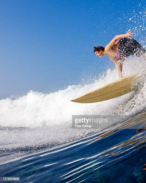 Young surfer catching wave