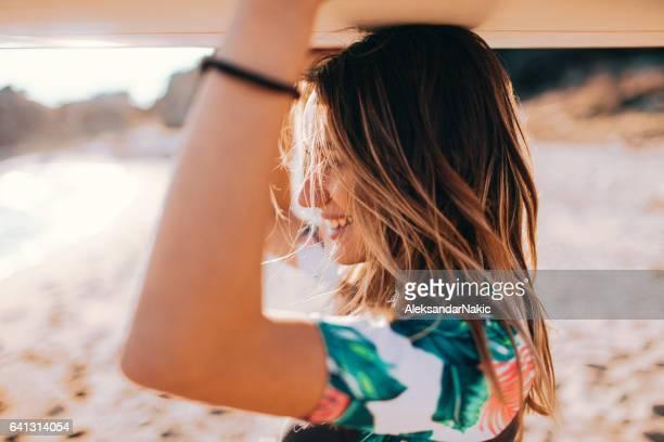 若いサーファーの女の子と彼女のサーフボード