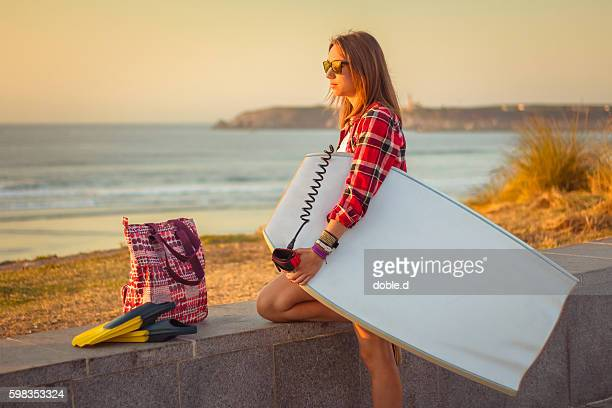 Young surfer girl holding bodyboard and looking the sea