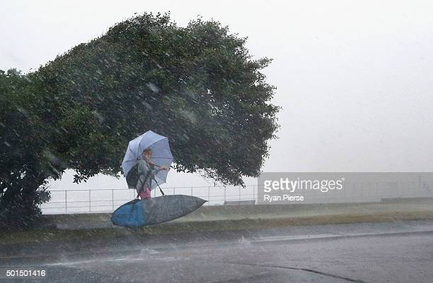 A young surfer leaves as a storm hits Bondi Beach on December 16 2015 in Sydney Australia The Bureau of Meteorology issued a warning for tornadoes...