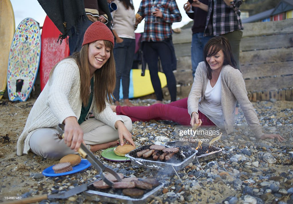 Young surfers cooking on barbecue at beach party. : Stock Photo