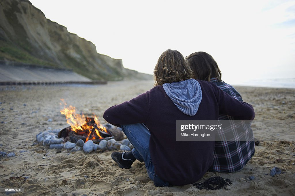 Young surfing couple on beach by fire. : Stock Photo