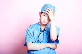 Young   surgeon wearing scrubs and looking stressed