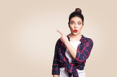 Young surprised girl with casual style and bun hair pointing her finger sideways, demonstrating something on beige blank wall with copy space for your information or promotional content.