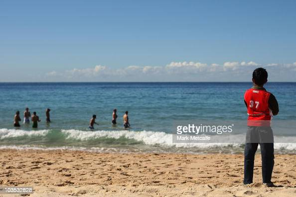 A young Swans fan watches the Sydney Swans walk along the surf during a Sydney Swans AFL recovery session at Coogee Beach on August 22 2010 in Sydney...