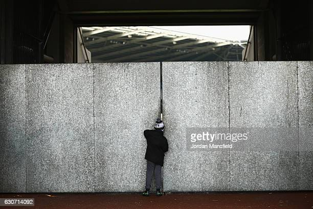 A young Swansea City supporter is seen watching inside the stadium from the gap of the walls prior to the Premier League match between Swansea City...
