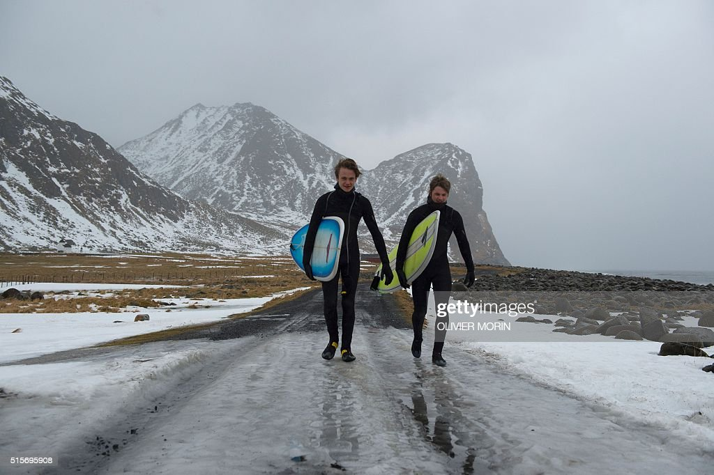Young Swedish surfers go to the water at the end of afternoon, after spending the night under a tent at the snow covered beach Unstad in Lofoten Island, Arctic Circle, on March 12, 2016. Surfers from all over the world come to Lofoten island to surf in extrem conditions. Ocean temperature is 5-6 °C, air temperature around 0°C in spite of a weather very unstable. / AFP / OLIVIER