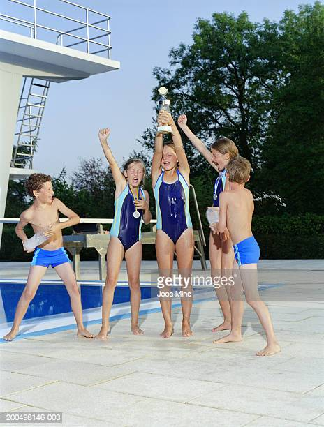 Young swimming team (9-10) with trophy celebrating by pool