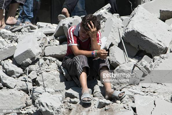 A young Syrian boy cries as he sits on the rubble after a missile fired by Syrian government forces hit a residential area in the Maghayir district...