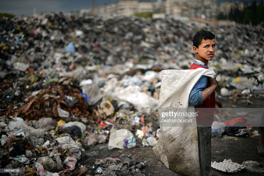 A young Syrian boy holds a bag as he collects plastic and metal items in a garbage dump in the northern Syrian city of Aleppo on April 17, 2013. Russian Foreign Minister Sergei Lavrov criticised the Friends of Syria grouping of Western and Arab countries opposed to the rule of President Bashar al-Assad as negative for dialogue. AFP PHOTO / DIMITAR DILKOFF