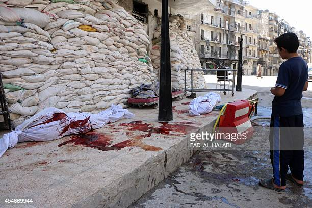 A young Syrian boy looks at bodies lying outside a hospital following an alleged Syrian government barrel bomb attack in the northern Syrian city of...