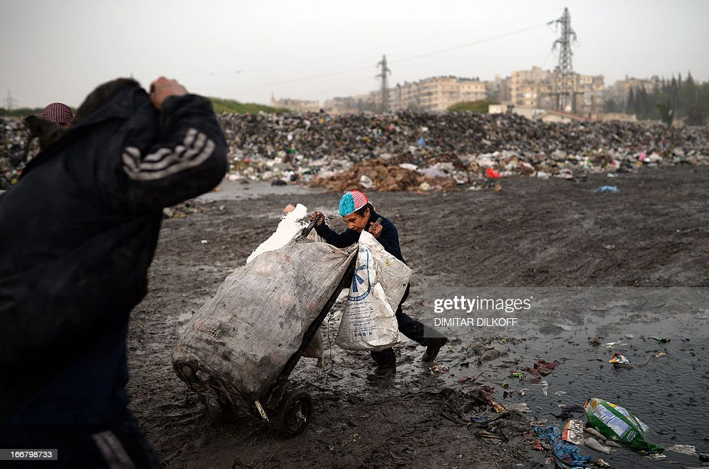 A young Syrian boy pushes a cart after collecting plastic and metal items in a garbage dump in the northern Syrian city of Aleppo on April 17, 2013. Russian Foreign Minister Sergei Lavrov criticised the Friends of Syria grouping of Western and Arab countries opposed to the rule of President Bashar al-Assad as negative for dialogue. AFP PHOTO / DIMITAR DILKOFF
