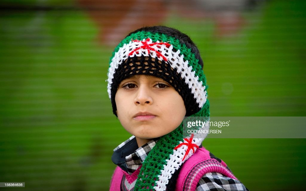 A young Syrian boy wearing a scarf bearing the colours of the pre-Baath Syrian flag looks on in the northern town of Darkush on December 14, 2012. The United States said it plans to deploy two Patriot missile batteries to Turkey along with 400 troops to help defend its ally against potential threats from neighbouring Syria. AFP PHOTO / ODD ANDERSEN