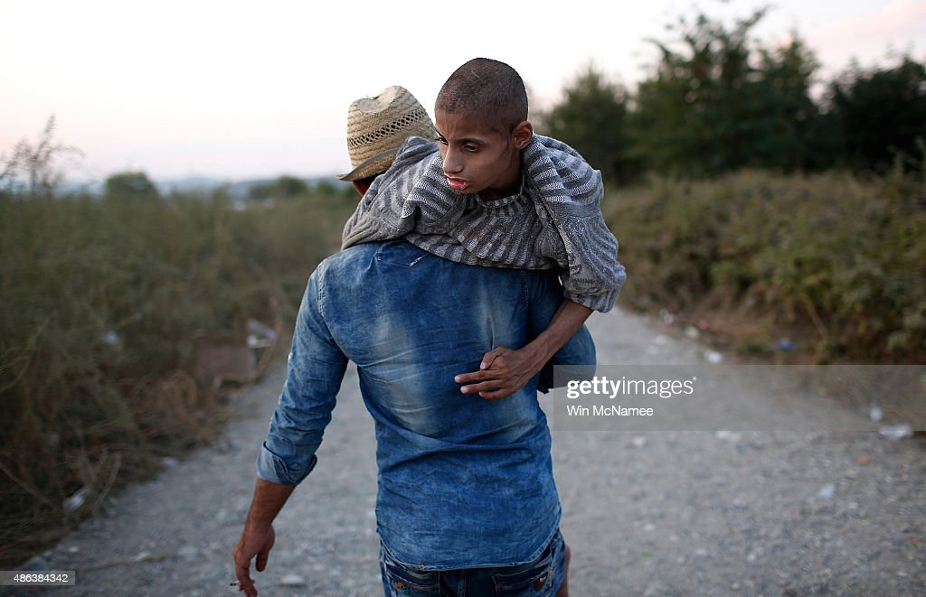 A young Syrian boy with Cerebral Palsy is carried by his brother after his family crossed the Macedonian border from Greece September 3, 2015 in Gevgelija, Macedonia. From Gevgelija most migrants continue to work their way north to the border with Serbia by either train, bus or taxi. Since the beginning of 2015 the number of migrants using the so-called 'Balkans route' has exploded with migrants arriving in Greece from Turkey and then travelling on through Macedonia and Serbia before entering the EU via Hungary. The number of people leaving their homes in war torn countries such as Syria, marks the largest migration of people since World War II.