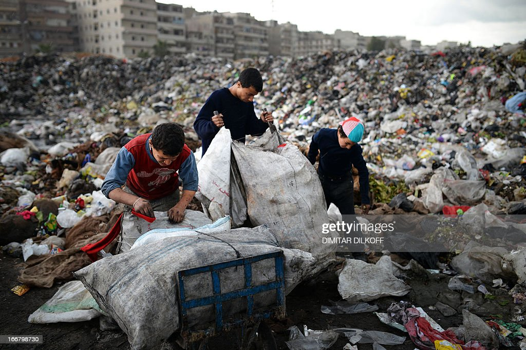 Young Syrian boys collect plastic and metal items in a garbage dump in the northern Syrian city of Aleppo on April 17, 2013. Russian Foreign Minister Sergei Lavrov criticised the Friends of Syria grouping of Western and Arab countries opposed to the rule of President Bashar al-Assad as negative for dialogue. AFP PHOTO / DIMITAR DILKOFF
