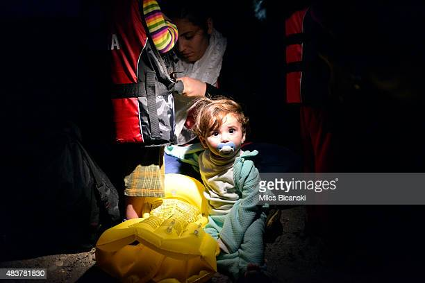 A young Syrian child looks at the camera as migrants arrive at a beach on the Greek island of Kos after crossing a part of the Aegean sea from Turkey...