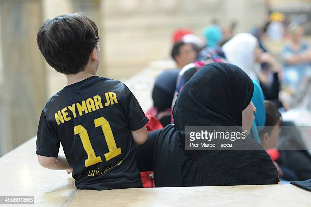 A young Syrian child wears his Neymar Jr tshirt while waiting amongst the crowd with all Syrian refugees who arrived by train to the Milano Centrale...