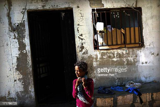 A young Syrian girl from the city of Homs stands outside a home shares with family members inside a camp for Syrians who have fled the fighting in...