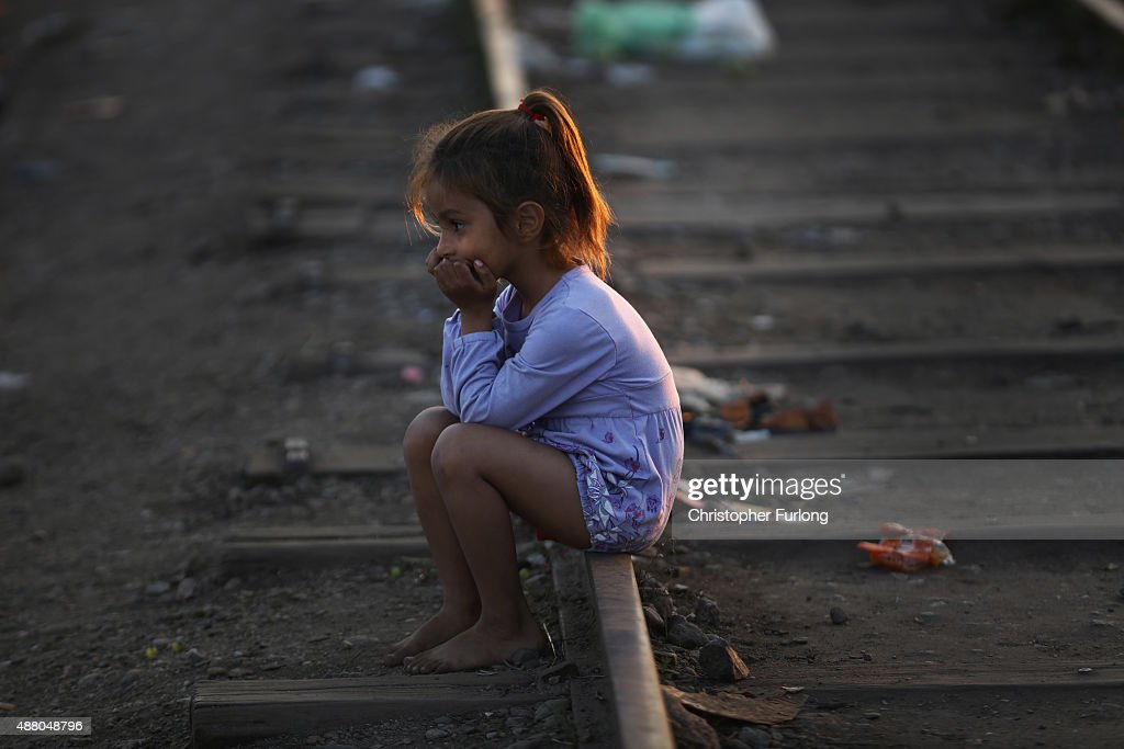 A young syrian girl sits on the tracks at the Serbian border with Hungary as she and her family wait for darkness before heading across country in Hungary. Although shoeless the little girl was in good spiritis on September 13, 2015 in Roszke, Hungary. A record number of 4000 people crossed the border yesterday. Migrants are rushing to the Hungarian border due to fears and rumours that the borders will soon close before the official closure of midnight on Monday. Germany has also announced that it will be implementing temporary border controls with Austria to try and administer the influx of migrants. Since the beginning of 2015 the number of migrants using the so-called 'Balkans route' has exploded with migrants arriving in Greece from Turkey and then travelling on through Macedonia and Serbia before entering the EU via Hungary. The number of people leaving their homes in war torn countries such as Syria, marks the largest migration of people since World War II.