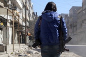 A young Syrian journalist carries a camera and a gun to protect himself notably from kidnappings on February 9 2014 in a street in the northern...