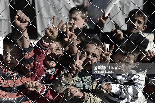 Young Syrian Kurdish boys make the 'V for victory' sign behind a fence at a refugee camp in the town of Suruc Sanliurfa province on November 5 2014...