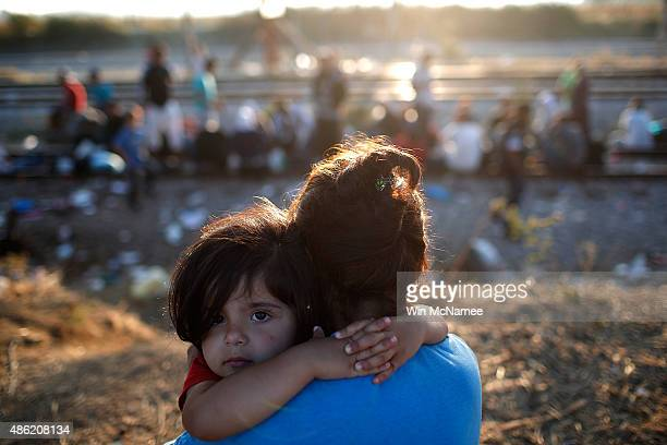 A young Syrian migrant girl is held by her mother next to railroad tracks where migrants wait to cross into Macedonia September 2 2015 in Idomeni...