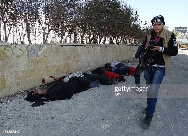 A young Syrian photojournalist walks past bodies of handcuffed and blindfolded dead men laying on the ground of the Aleppo headquarters of the...