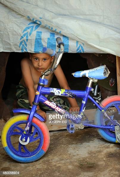 A young Syrian refugee boy looks out from a shelter at an informal refugee camp in the area of Zahrani south of the Lebanese capital Beirut on July 9...