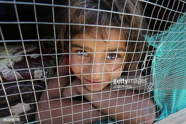 A young Syrian refugee girl looks out from her shelter at an informal refugee camp in the area of Zahrani south of the Lebanese capital Beirut on...