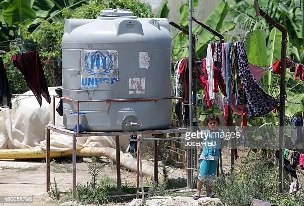 A young Syrian refugee girl stands near a water container at an informal refugee camp in the area of Zahrani south of the Lebanese capital Beirut on...