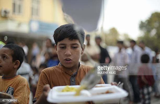 A young Syrian refugee lines up for food as Syrians break their fasting on June 20 2015 in Akcakale in Sanliurfa province during the holy month of...